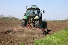 Cultivo de un campo con un tractor Imagen de archivo libre de regalías