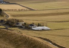 Cultivo tradicional en Islandia Balas redondas blancas con la hierba que miente cerca de una granja en una hierba amarilla seca e imagen de archivo libre de regalías