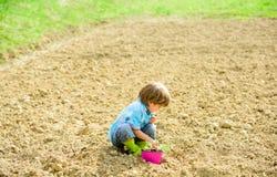 Cultivo y agricultura D?a de tierra suelos y fertilizantes Granja del verano Jardinero feliz del ni?o Pueblo de la primavera ecol fotos de archivo libres de regalías