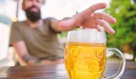 Cultura distinta da cerveja Cerveja fresca fria da caneca no fim da tabela acima O homem senta o terra?o do caf? que aprecia cerv imagem de stock
