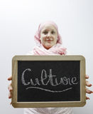 Cultural difference. Young caucasian woman dressed in pink arab clothes holding blackboard with culture word in hands Stock Photography