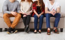 Culture de jeunes amis s'asseyant sur le divan à l'intérieur Images stock