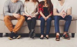 Culture de jeunes amis s'asseyant sur le divan à l'intérieur Photo libre de droits