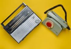 Culture des années 70 Récepteur radioélectrique et téléphone rotatoire sur le fond jaune Rétro dispositifs Vue supérieure Photographie stock