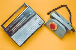 Culture of the 70s. Radio receiver and rotary telephone. On yellow background. Retro devices. Top view stock image