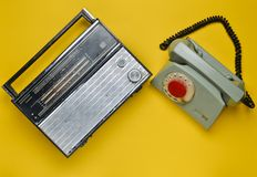 Culture of the 70s. Radio receiver and rotary telephone on yellow background. Retro devices. Top view.  Stock Photography