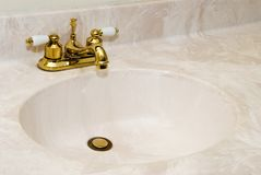 Cultured Marble Sink with Gold Faucet. New cultured marble bathroom sink with gold finish faucet and copy space Stock Photo