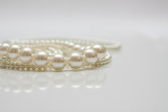 Cultured pearls on white. Background shallow dof Royalty Free Stock Image