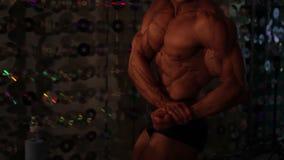 Culturista abbronzato profondo che dimostra il grande bicipite, mancanza di grasso corporeo, forma fisica stock footage
