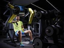 Culturista adulto joven feliz que hace el levantamiento de pesas en gimnasio Imagen de archivo libre de regalías