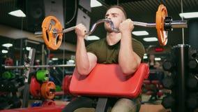 Culturista adulto joven que hace el levantamiento de pesas entrenando a su bíceps en gimnasio Al borde de posibilidades Tirado en almacen de video