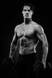 Culturista atletico del tipo di potere bello che fa gli esercizi con il dum Fotografia Stock