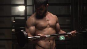 Culturista caucásico que se resuelve con el Barbell en gimnasio almacen de metraje de vídeo