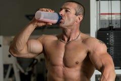 Culturista che beve da una bottiglia di acqua Immagini Stock Libere da Diritti