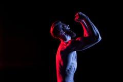 Culturista che gesturing e che urla isolato sul nero con illuminazione drammatica fotografia stock