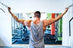 Culturista che risolve il bicipite nella palestra weightlifting fotografie stock libere da diritti