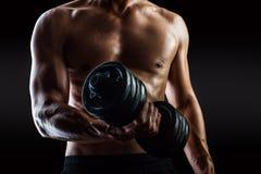 Culturista con las gotas del entrenamiento del sudor en gimnasio Imagen de archivo libre de regalías