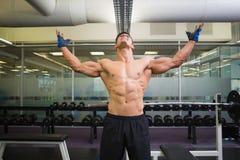 Culturista con los brazos aumentados en gimnasio Fotos de archivo libres de regalías