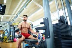 Culturista con pesas de gimnasia en el gimnasio imágenes de archivo libres de regalías