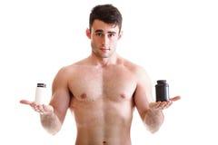 Culturista de sexo masculino atractivo sosteniendo las cajas con suplementos en su b Imágenes de archivo libres de regalías