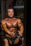 Culturista de sexo masculino que hace el ejercicio pesado para la parte posterior Foto de archivo