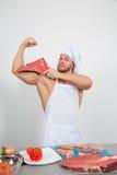 Culturista del cocinero que prepara pedazos grandes de la carne cruda proteínas naturales Fotografía de archivo libre de regalías