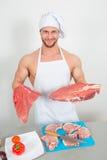 Culturista del cuoco unico che prepara i grandi bei pezzi di carne cruda proteine naturali Immagini Stock