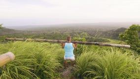 Culturista del hombre que se pone en cuclillas con el barbell de madera mientras que entrenamiento al aire libre en las zonas tro metrajes