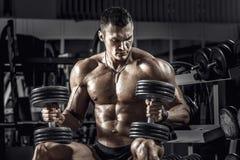 Culturista del individuo con pesa de gimnasia imagen de archivo