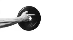 Culturista dell'atleta, tenente a disposizione un disco per le teste di legno, poin Fotografia Stock Libera da Diritti