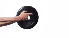 Culturista dell'atleta, tenente a disposizione un disco per le teste di legno, poin fotografia stock