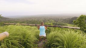 Culturista dell'uomo che occupa con il bilanciere di legno mentre addestramento all'aperto nei tropici Uomo di sport che prepara  stock footage