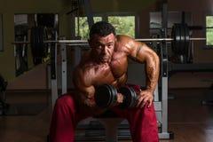 Culturista descamisado que hace el ejercicio pesado para el bíceps Foto de archivo
