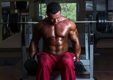 Culturista descamisado que hace el ejercicio pesado para el bíceps Fotos de archivo libres de regalías