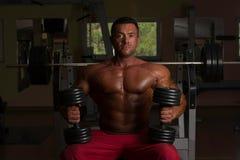 Culturista descamisado que presenta con pesa de gimnasia en el banco Fotografía de archivo