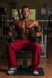 Culturista descamisado que presenta con pesa de gimnasia en el banco Imagenes de archivo