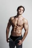 Culturista di modello maschio muscolare con i jeans sbottonati Studio SH Fotografie Stock