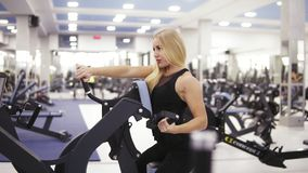 Culturista femenino joven en la ropa de deportes negra que hace exersices en el gimnasio Acumulación de los músculos fuertes de l almacen de metraje de vídeo