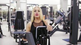 Culturista femenino joven en la ropa de deportes negra que hace exersices en el gimnasio Acumulación de los músculos fuertes de l metrajes