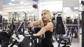 Culturista femenino joven en la ropa de deportes negra que hace exersices en el gimnasio Acumulación de los músculos fuertes de l almacen de video