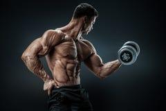 Culturista fuerte y del poder que hace ejercicios con pesa de gimnasia Foto de archivo