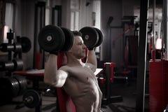 Culturista hermoso con entrenamiento muscular del torso con pesas de gimnasia en banco atlético en gimnasio Cuerpo masculino musc Imagen de archivo