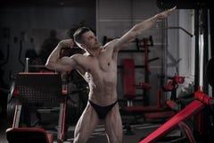 Culturista hermoso que presenta en gimnasio Cuerpo masculino muscular perfecto Imagen de archivo libre de regalías