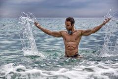 Culturista joven hermoso en el mar, salpicando el agua para arriba Imagenes de archivo
