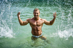 Culturista joven hermoso en el mar, salpicando el agua para arriba Imagen de archivo libre de regalías