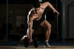 Culturista joven que levanta pesa de gimnasia pesada Fotos de archivo
