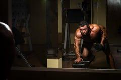 Culturista maschio che fa esercizio pesante per la parte posteriore Fotografia Stock
