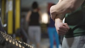 Culturista maschio che massaggia braccio, distorsione di sofferenza del polso durante l'allenamento in palestra stock footage