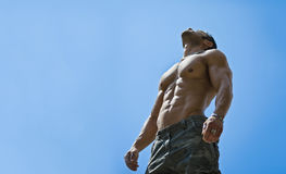 Culturista maschio muscolare senza camicia su cielo blu Fotografia Stock