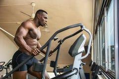 Culturista maschio nero muscolare che si esercita sulla macchina di punto in palestra Fotografia Stock
